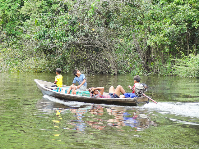 Peruvian children boating up the Amazon River