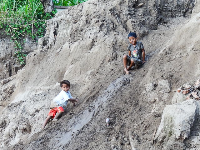Children using the river bank as a slide.